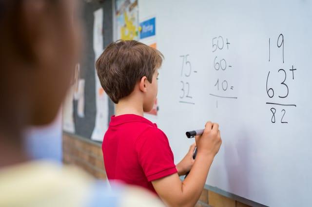 Boy doing maths on a white board